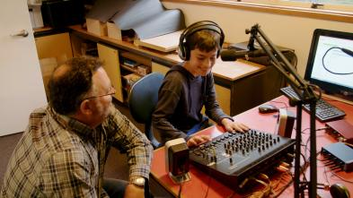 Parent and student sitting at a desk with audio equipment