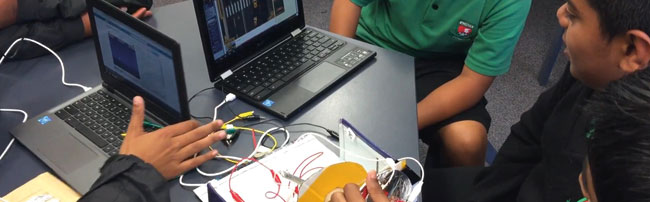 students creating with laptops and makey-makey