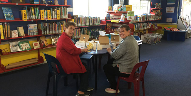 teacher aides creating learning packs in a school library