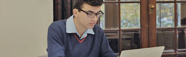a student studying with an open laptop