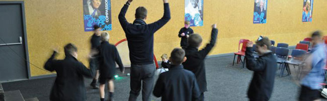 Students and teacher dancing with arms raised