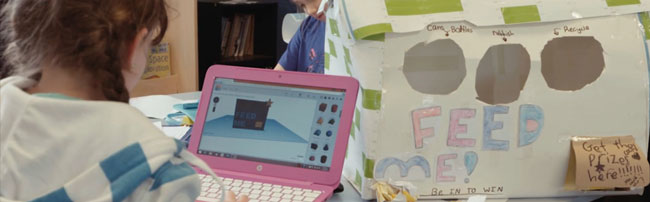 a child designing on a laptop, a cardboard model beside her