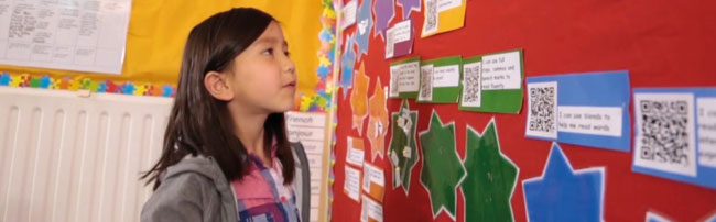 A student examining a wall display containing QR codes