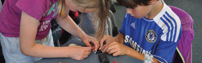 Two children working intently on a STEAM project