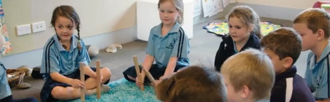 Students playing with rakau on the mat