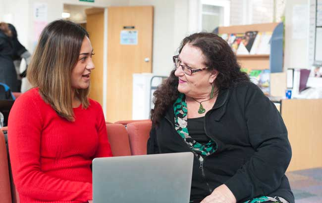 Two teachers discussing with a laptop