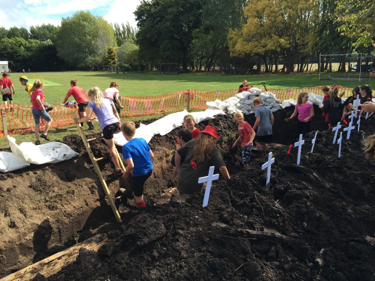 Students climbing in trenches they have dug