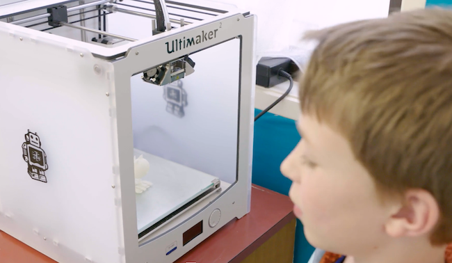 Student looking at 3D printer.