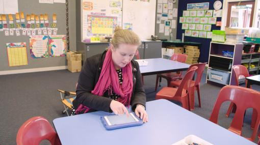 Teacher, Emma Jensen working at a desk on an iPad