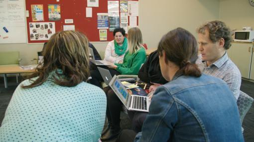 Teachers work together on laptops