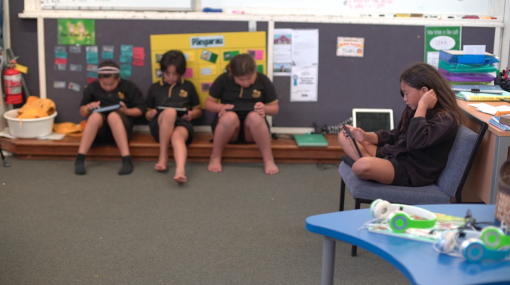 Three students sitting on the floor using iPads and one student sitting on a seat using an iPad
