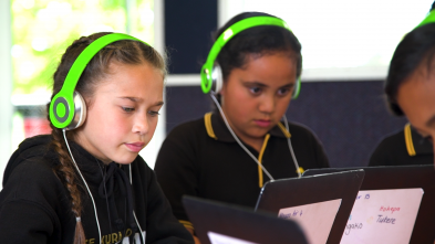 Two students working on laptops wearing green headphones