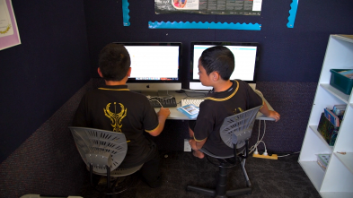 Two boys sitting in front of computers