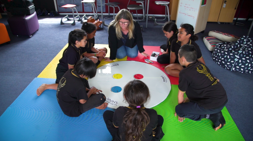 Students working on an activity on the floor with the teacher