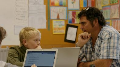 Teacher talking with a student working on his laptop